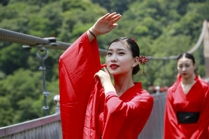 Female graduates dressed in traditional Chinese costumes pose for graduation photos on the glass bridge at the Tianlongchi scenic area in Pingdingshan, Henan province, on June 18. Photo: IC
