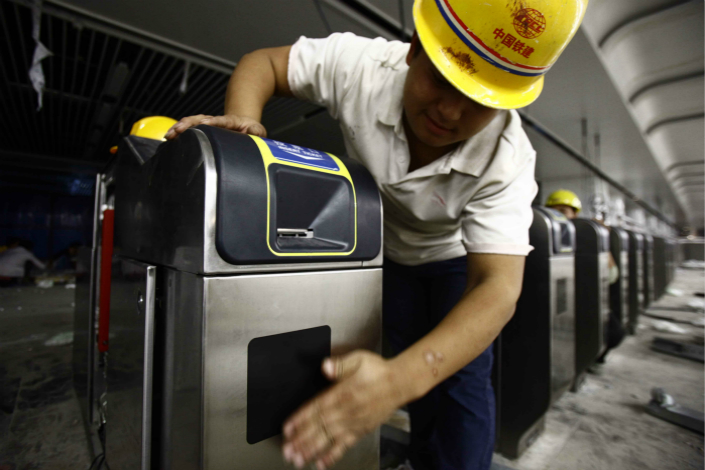 Beijing municipal authorities have rolled out promotions for a new program that allows subway riders that use certain Android cellphones to pay fares with their phones at all of the city's subway stations. Above, workers install fare gates in a Beijing subway station in October 2011. Photo: Visual China