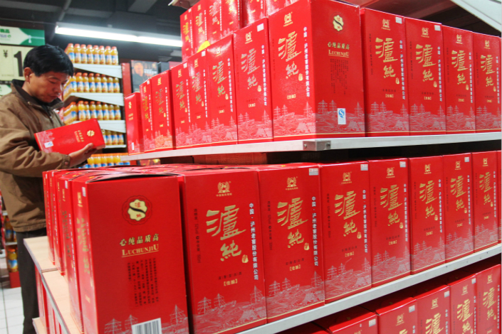 Luzhou Laojiao will spend the equivalent of about $60 million after taxes to acquire a former school property for a themed-village project that will be on about 8 acres in the liquor-maker's hometown of Luzhou, Sichuan province. Above, a customer shops for Luzhou Laojiao liquor in a supermarket in Xuchang, Henan province, in November 2012. Photo: Visual China