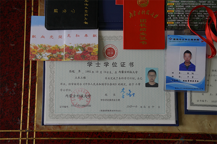 Zhang Chao's diploma, degree certificate, and materials about his activity as a student leader are displayed. Zhang, 25, was found dead on the side of a rural road in Tianjin on July 14, a death police say was caused by heatstroke, and one of several recent deaths police say are linked to pyramid sales networks. Photo: Yang Yifan/Caixin