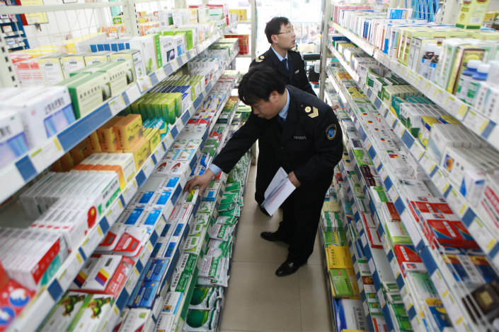 Under new legal interpretations, researchers convicted of falsifying data in studies or clinical trials for new medications could face up to 10 years in prison. Above, drug administration officials in Jiujiang, Jiangxi province, inspect medicines in a pharmacy in April 2012. Photo: Visual China