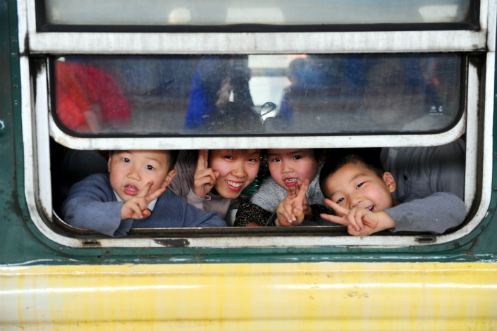 The State Council said in a statement Wednesday that it will clarify the timetable to broaden overseas investors' access to the financial sectors and nine other industries, including passenger rail transportation, but did not specify a date. Above, young passengers peer from a train window in Guangzhou, Guangdong province, in January 2013. Photo: Visual China