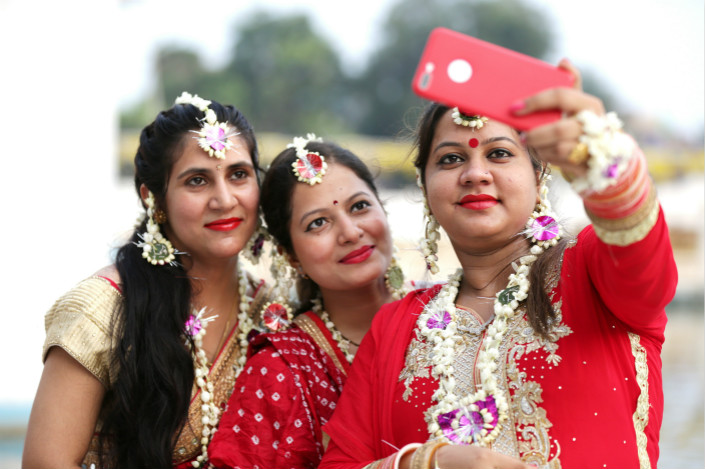Xiaomi consolidated its position as the Indian market's clear No. 2 seller, behind only Samsung, by posting 25% year-on-year growth to command 17% of the market in the second quarter, while Vivo posted similar growth to finish third with 13%. Above, newly married Indian women take selfies with a cellphone as they visit the Lakshmi Narayan Temple in Amritsar, India, on July 16 during the Teej festival. Photo: IC