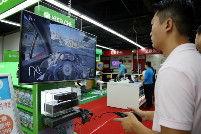 While video-game consoles and games are a small business in China compared with the online-gaming industry, many observers point to a growth rate for consoles that is well above the industry average. Above, a customer tries out an Xbox One game console at a Suning home appliances store in Shanghai in September 2014. Photo: IC