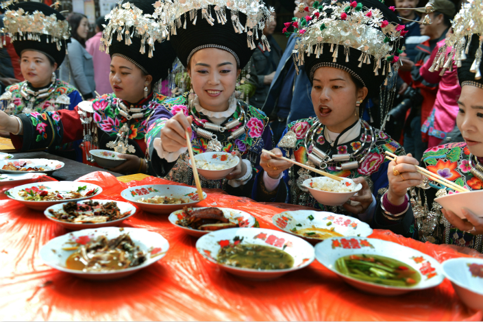 Women of the Miao ethnic group eat at a Long Table Banquet. Photo: IC