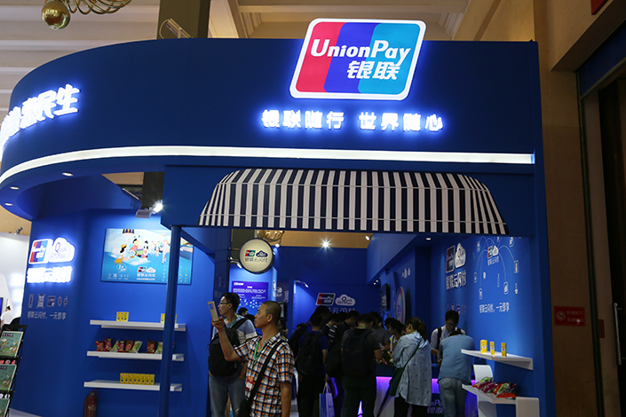 UnionPay's recent move to tie bank cards to online retailer JD.com Inc. has called into question the division between China's two cashless-payment clearing systems. Above, UnionPay hosts a table at the 25th China International Financial Exhibition in Beijing on July 27. Photo: Visual China