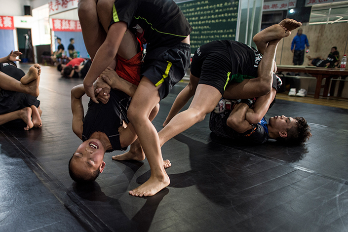 Although most of the Enbo Fight Club's activities are government-sanctioned, Chengdu police opened an investigation into the mixed martial arts group after a video showing two 14-year-old boys in a bruising cage fight went viral last week. Above, boys grapple during a training session at the Enbo Fight Club in Chengdu, Sichuan province. Photo: Visual China.