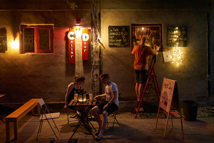 A customer buys a drink through a small window in the Cellar Door pub in Fangjia Hutong in downtown Beijing. The pub, which is popular among expatriates and tourists for its cheap drinks, recently had its door walled up as part of a Beijing government crackdown on illegal construction, including doors and windows that were added for business purposes. The city government plans to wall up or demolish about 16,000 such places this year. Still, businesses such as the Cellar Door continue to operate. Photo: Liang Yingfei/Caixin