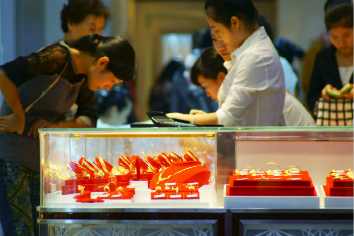JD.com Inc., Citic Securities, Industrial Bank Co. Ltd., and five other private companies will buy a major stake in China National Gold Group Corp.'s jewelry unit. Above, customers buy gold jewelry from China National Gold shops in Yichang, Hubei province, in September 2014. Photo: IC