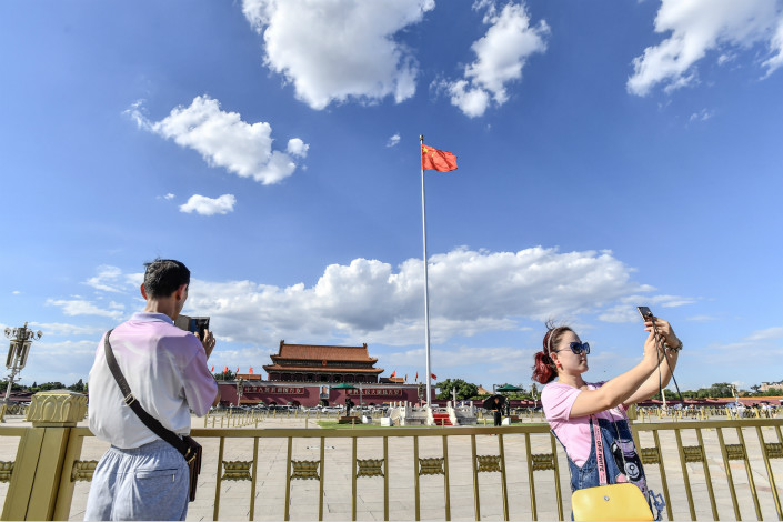The Ministry of Environmental Protection has unveiled a plan in which the number of heavily polluted days in China's northeast will be reduced 15% from October to March. Above, Beijing tourists take photos under clear blue skies at Tiananmen Square on Aug. 6. Photo: IC