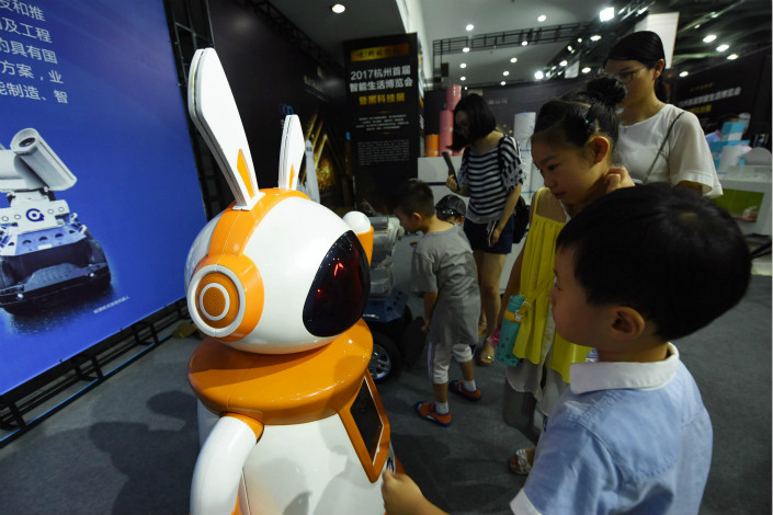 A new PricewaterhouseCoopers report says that 59 technology, media and telecommunications firms went public from January through June, raising a total of 25.8 billion yuan ($3.91 billion). Above, visitors at a technology expo interact with artificial-intelligence robots in Hangzhou, Zhejiang province, on Friday. Photo: Visual China
