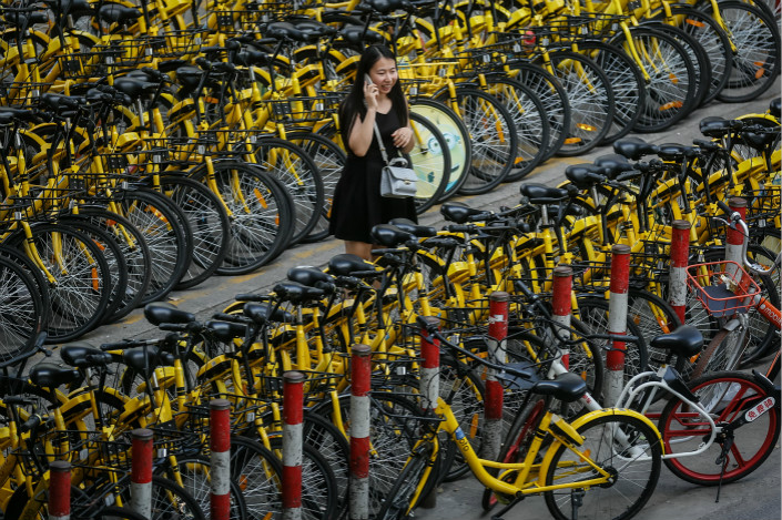 Shenzhen, Shanghai, Zhengzhou, Hangzhou and Nanjing are among the Chinese cities that are acting to address the growing problem of shared bicycles' cluttering their streets. Above, a Shanghai sidewalk is crowded with Ofo Inc.'s distinctive yellow shared bicycles on Aug. 23. Photo: Visual China