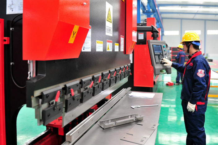 Of the14 machine tool firms listed on either the Shanghai or Shenzhen stock exchanges, eight reported profit growth in the first half of 2017 compared with the same period last year. Above, a worker enters data into an automated machine tool control system in Yichang, Hubei province, in January 2015. Photo: Visual China