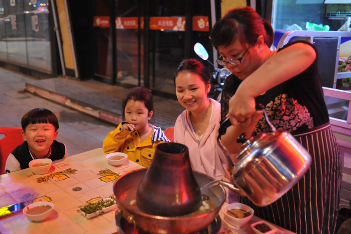 A waitress pours soup into a hot pot container while customers wait for their dinner at a restaurant in Chongli, a ski-resort town more than 200 kilometers (124.2 miles) to the northwest of Beijing. Photo: Wu Gang/Caixin