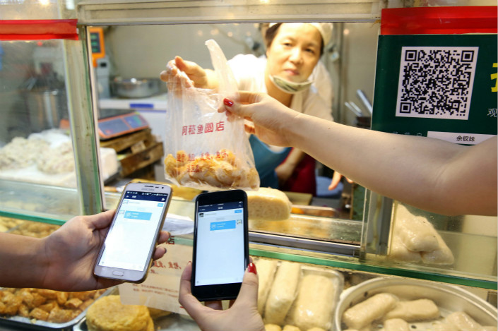 More than 39.42 trillion yuan was paid via mobile devices in the second quarter this year, up 33.84% from a year ago, the People's Bank of China said. Above, customers take their purchases after paying via mobile-payment service Alipay at a market in Wenzhou, Zhejiang province, in September 2015. Photo: IC