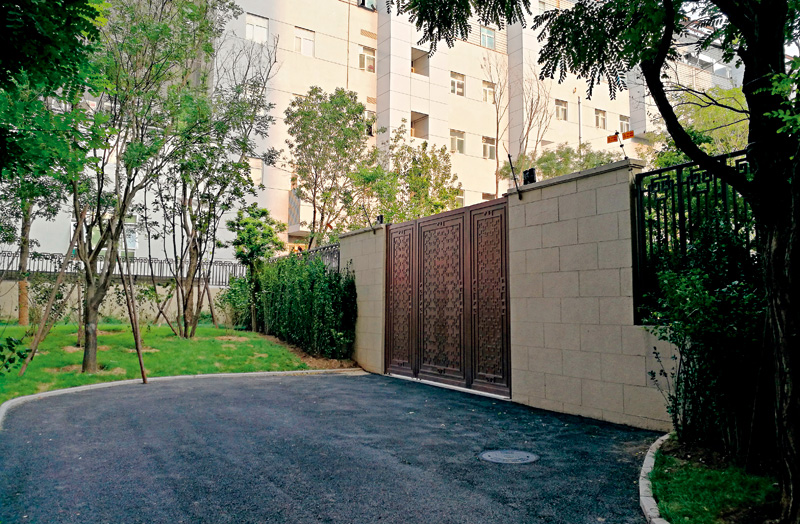 On one side of the gated wall (pictured) dividing a residential compound in Beijing, homes were sold to low-income families for 21,000 yuan ($3,150) per square meter. On the other side, residents spent between 100,000 and 160,000 yuan a square meter for an area with far more lush green space. Photo: Huang Ziyi