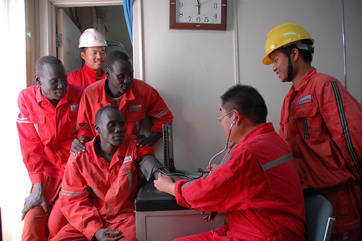 The state-owned Sinopec has poured billions into overseas assets in recent years, including many in Africa. The above picture shows the oil firm's employees conducting a physical examination in Sudan in 2008. Photo Visual China