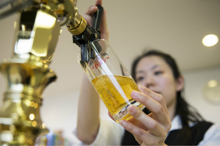 Asahi Group Holdings Ltd.'s plans to sell all its shares in Tsingtao Brewery Co. Ltd. is the latest in a series of the Japanese brewer's recent divestments from Chinese companies. Above, a bartender pours a glass of Asahi Super Dry beer at the Asahi Kanagawa Brewery in Minamiashigara, Kanagawa prefecture, Japan, on March 6. Photo: Visual China