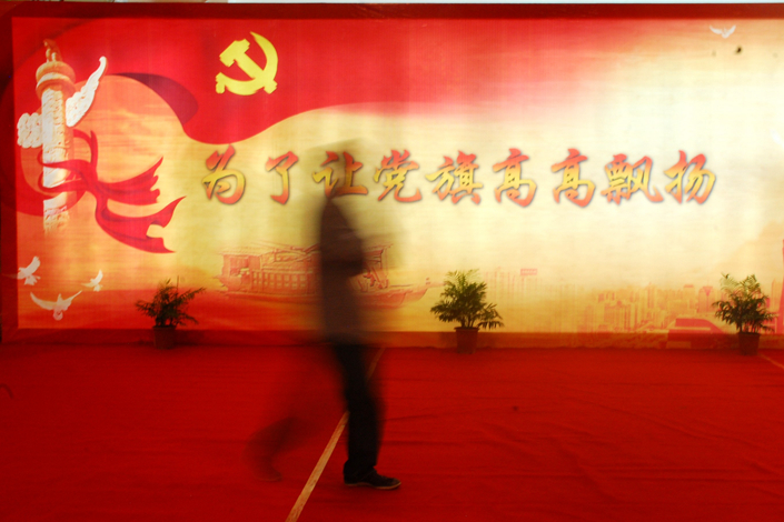 An official exhibit of the Communist Party's achievements in Beijing hinted that five unnamed members of the Central Committee may be in as-yet-unrevealed trouble. Above, a passerby walks beside a display reading