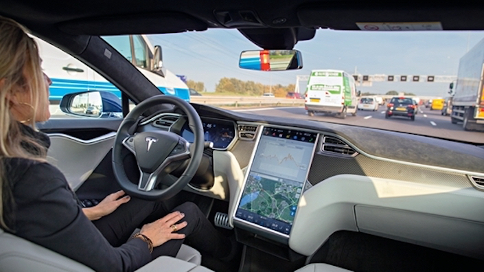 A Tesla employee tests the company's car autopilot function in Amsterdam in October 2015. Photo: Visual China