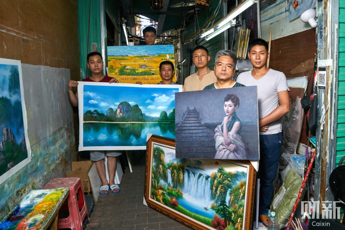 Workers in Dafen, Shenzhen, pose with their artwork. Thirty-seven-year-old Zhang Zhibin (third from left) has worked in painting workshops around the country, but decided to settle in Dafen due to the size of its industry. 50-year-old Li Hongmin (second from right) started his artistic career in Dafen in 1991, and has watched the village grow since then.
