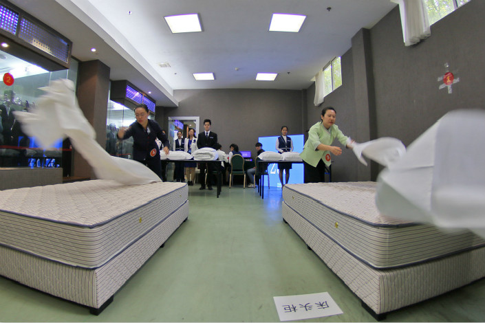 The Caixin China Composite Output Index, which covers manufacturing and services companies, saw its weakest expansion in 16 months in October. Above, a hotel-room service competition takes place in Yantai, Shandong province, in October 2016. Photo: Visual China