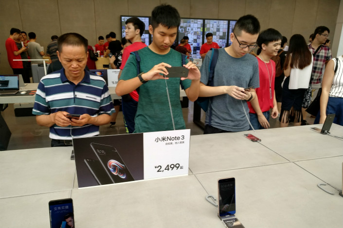 Smartphone-maker Xiaomi Inc. doubled its sales in the third quarter, boosting its global market share to 7.4%. Above, Xiaomi customers try out the company's smartphones at its flagship store in Shenzhen on Sept. 27. Photo: Visual China