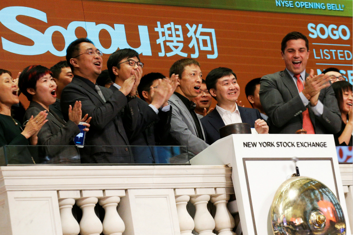 Shares of Sogou Inc. initially rose as much as 13% when the stock began trading on Thursday in New York City, but later gave back most of the gains. Above, Sogou Chairman Charles Zhang (center, in gray jacket) and CEO Wang Xiaochuan (second from right, in white shirt) ring the opening bell at the New York Stock Exchange on Thursday. Photo: Visual China