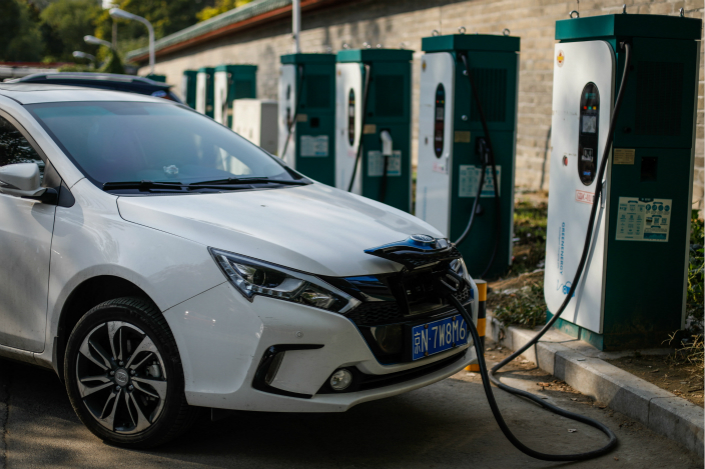 The current 50% limit in the stake that foreign companies can have in carmaking factories in China will be lifted as long as the companies are producing new-energy cars in free trade zones. Above, an electric car charges at a station in Beijing on Oct. 23. Photo: IC