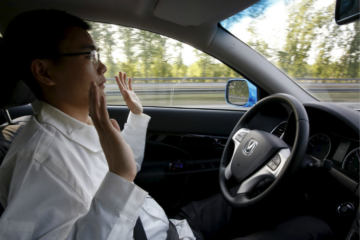 Automakers are looking to take advantage of internet companies' big data and mapping expertise. Changan has partnered with firms such as  Huawei, Baidu, Tencent, Alibaba and Intel to build 'smart cars.' Pictured is a Changan engineer road-testing a driverless car on a Beijing highway. Photo: Visual China