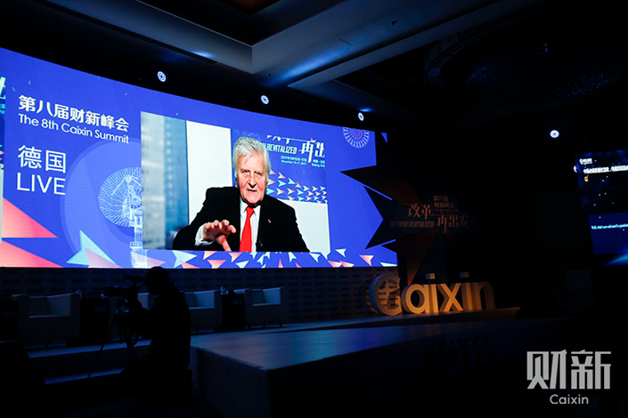 Jean-Claude Trichet, chairman of the Group of 30 and former president of the European Central Bank, speaks through satellite transmission at the 8th Caixin Summit on Wednesday. Trichet called for vigilance against excessive leverage. Photo: Caixin