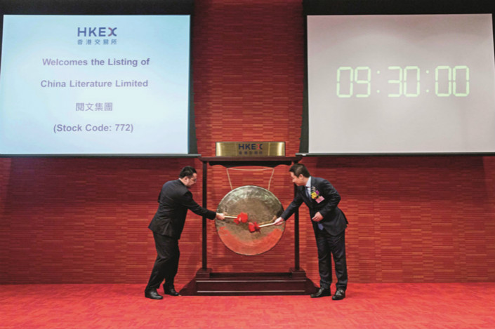 China Literature Co-CEOs Liang Xiaodong (right) and Wu Wenhui (left) bang a gong to launch the company's initial public offering on the Hong Kong Stock Exchange on Nov. 8. Photo: Visual China