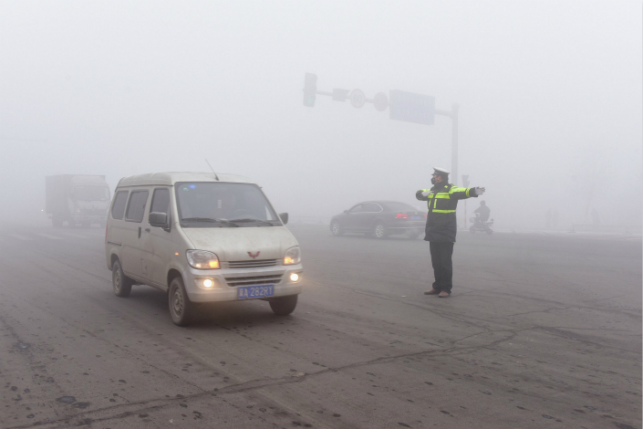 The concentration of PM2.5 in the air of the region that encompasses Beijing, Tianjin and Hebei province from January through October rose 8.5% on average compared with the same period last year. Above, police in Shijiazhuang, Hebei province, directs traffic in smog on Jan. 3. Photo: IC