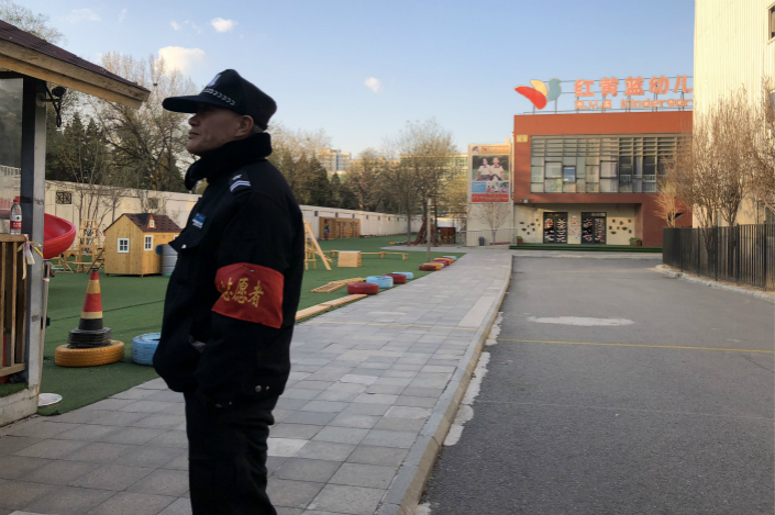 A security guard keeps a watchful eye in a kindergarten run by RYB Education Institution in eastern Beijing on Thursday. Some parents protested outside against alleged mistreatment of their children by teachers. Photo: Chen Weixi/ Caixin