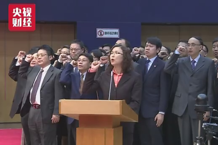 A screen grab of state television shows members of the new panel that reviews initial public offering applications getting sworn in at a ceremony on Nov. 20 in Beijing. Photo: CCTV