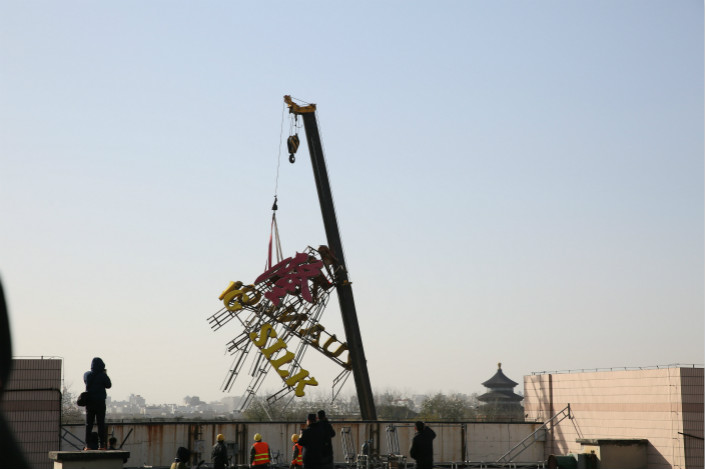 "As of the end of last week, nearly a third of the 27,000 noncompliant billboards have been removed from buildings in what authorities have called the ""skyline operation"" in Beijing. Above, a crane lifts a business sign off a building in Beijing on Nov. 28. Photo: Visual China"