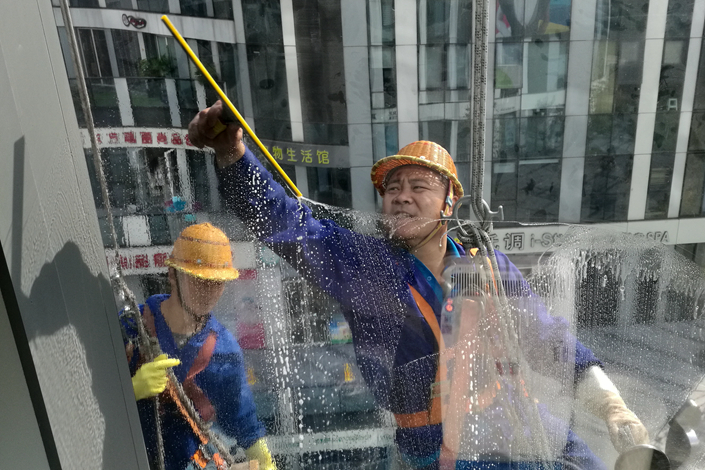 Window cleaners at work outside a building in Beijing on Oct. 12. Photo: Wu Gang/ Caixin