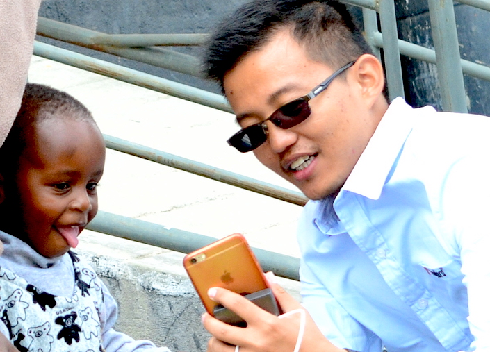 A Chinese businessman shows a smartphone to a child in Nairobi, Kenya. Photo: Richard Mungai, Mo Yelin, Xu Heqian