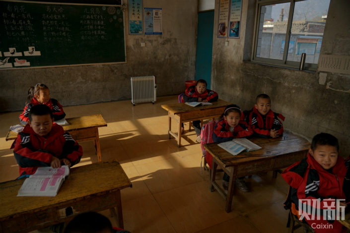 Jinzhang village's primary school is using a small electric heater as a temporary measure, but the classrooms are still very cold. Photo: Yang Yifan/Caixin