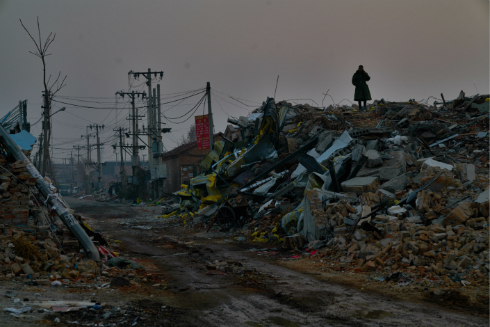 A man stands on the debris from demolished buildings in Xinjian village in Beijing's southern district of Daxing on Dec 2. A large number of buildings deemed to be illegal used for residential or businesses purposes were razed top the ground this area after a deadly fire in November, which killed 19. Photo: Liang Yingfei/Caixin