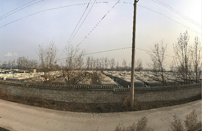 A large number of Xinyu Tourism Ltd. buses sit idle in a private parking lot near Linfen, Shanxi province, on Dec. 13, soon after media reported that empty Xinyu buses were running on Linfen's streets. Photo: An Limin/Caixin
