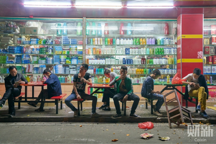 A group of Yi factory workers sit in front of a grocery store near their dorm in Dongguan, a manufacturing hub in Guangdong province. Since the early 1990's, thousands of Yi workers have left their isolated mountain villages to work in big cities. But language difficulties and their adherence to their own customs have led to discrimination, with many only being employed as temporary workers without health insurance or other benefits. Photo: Liang Yingfei/ Caixin