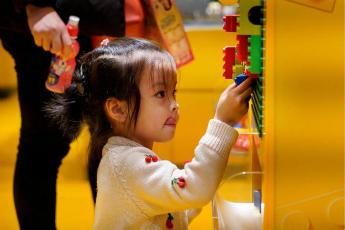 The Lego Group and Tencent Holdings Ltd. are stressing that the games, toys and cartoons they are jointly developing for Chinese children will be safe and wholesome. Above, a girl plays with Lego blocks in a Beijing store on Saturday. Photo: Visual China