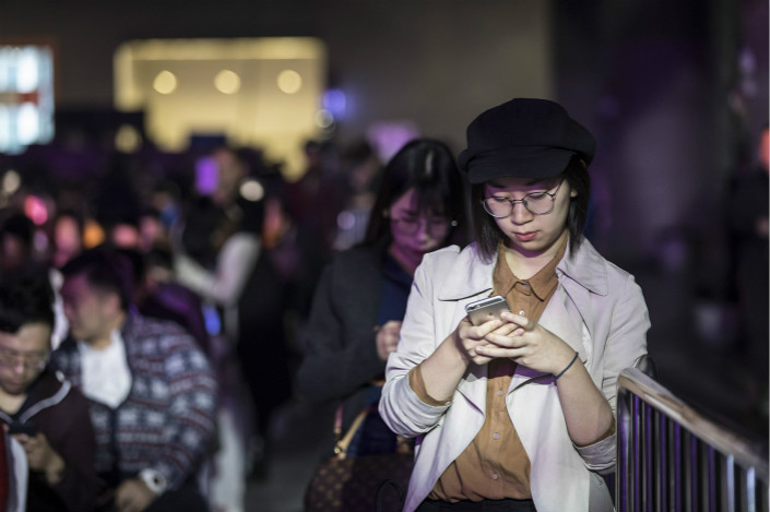 An attendee uses her smartphone on Monday at Tencent Holdings Ltd.'s WeChat Open Class Pro conference in the southern city of Guangzhou. Smartphone shipments in China fell nearly 10% in the first 11 months of 2017. Photo: Visual China
