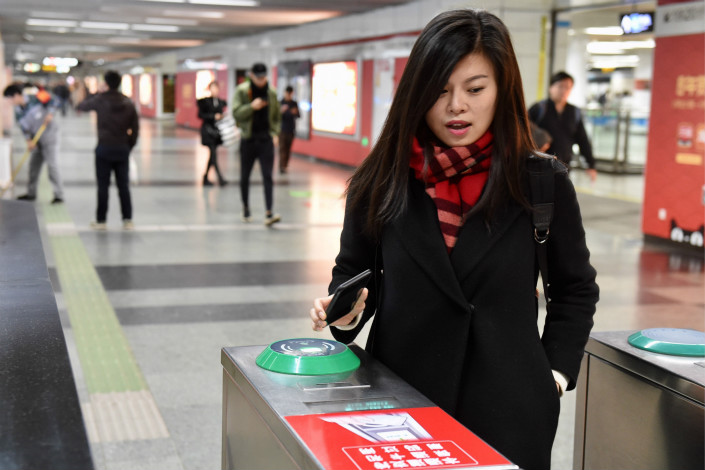 A Shanghai Metro customer uses a QR code to pay her fare at the Longyang Road Station on Tuesday. QR-code readers are being installed in all of Shanghai's 389 metro stations. Photo: IC