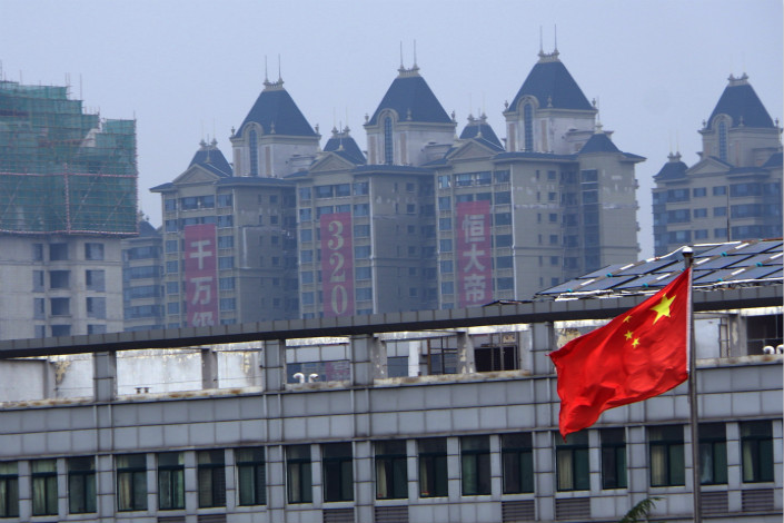 A Chinese national flag is seen in front of a high-rise residential project under construction in the city of Ji'nan, in east China's Shandong province, on Aug. 21, 2017. China's economy expanded by 6.9% in 2017, the first increase in growth in seven years. Photo: IC