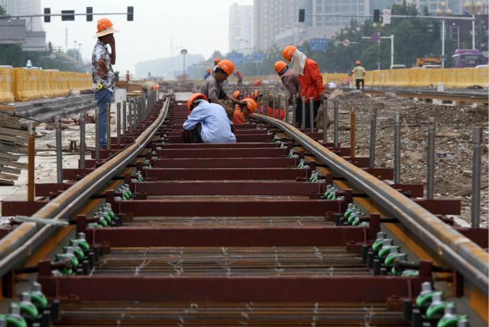 Workers in Huaian, Jiangsu province, lay down tracks for the city's light-rail system. A new government regulation says that insurance firms cannot provide funding to local governments through illicit means, and local governments will not be allowed to provide illegal guarantees to insurers. Photo: Visual China