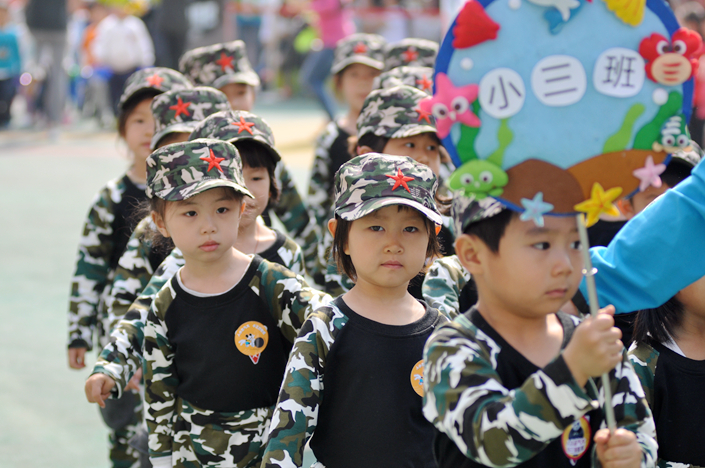 Kindergarteners in eastern Beijing walk in a parade for their school's sports meet in April 2016. Experts warn that a nationwide rush to build new preschools and kindergartens may have been premature. Photo: Wu Gang/Caixin
