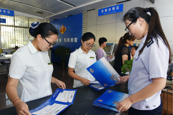 Workers sort mail at a local tax bureau in Rizhao, Shandong province. The convicted Beijing tax office employees helped people avoid sales taxes and personal income taxes imposed on existing homebuyers by tampering with tax declaration documents, the Beijing Commission for Discipline Inspection said. Photo: Visual China