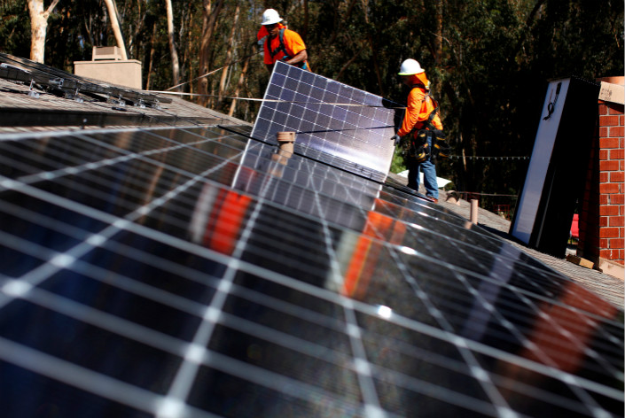 Workers install solar panels on the roof of a home in the U.S. in October 2016. A Chinese trade official said Wednesday that China is extremely dissatisfied with the U.S. decision to increase tariffs on products including solar panels. Photo: Visual China